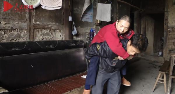 قصة رجل صيني حمل أمه المشلولة لمدة 15 عاما