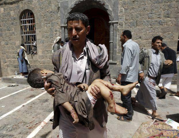 يمني يحمل طفله الشهيد في تفجيرات استهدفت المصلين بمسجدي بدر والحشوش بصنعاء 20 مارس 2015