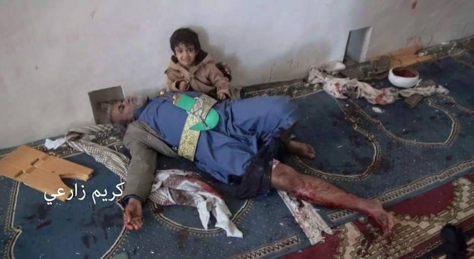 طفل إلى جانب والده الذي سقط في التفجيرات الإرهابية التي استهدفت المصلين بصنعاء يوم الجمعة 20 مارس 2015