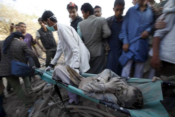 People carry a body from the rubble of a house destroyed by an air strike at the old quarter of Yemen's capital Sana'a