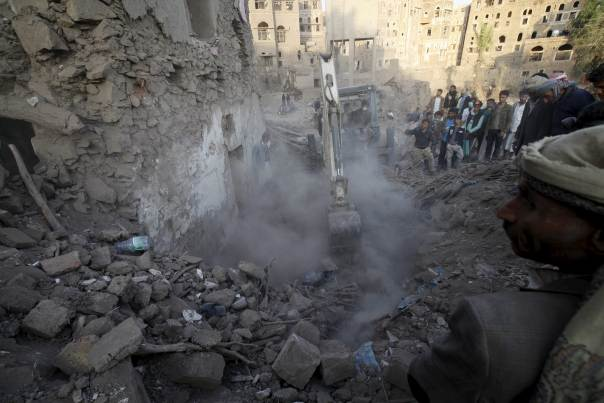 People search for survivors under the rubble of a house destroyed by an air strike at the old quarter of Yemen's capital Sanaa